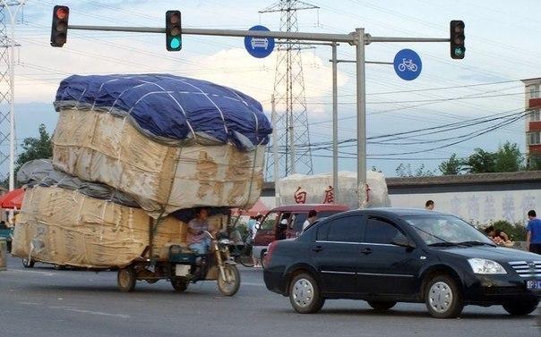 Мужчина ведет перегруженный трехколесный мотоцикл по оживленной улице в Пекине